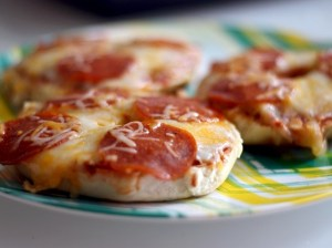 Four pizza bagels topped with pepperoni and cheese