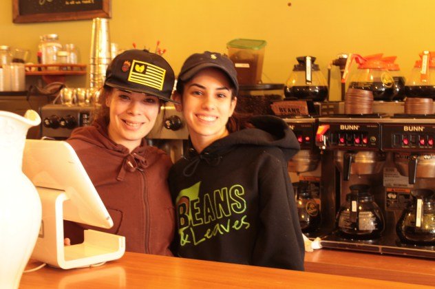 two baristas standing in front of coffee machines