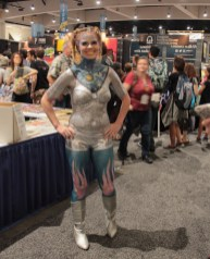 Girl covered in glitter dressed in silver shorts, bra and boots. Blue cosmic art painted on her chest and neck