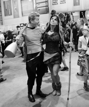 Captain Kirk with his arm around a female alien with teddy bear ears and a furry mini skirt holding a stick