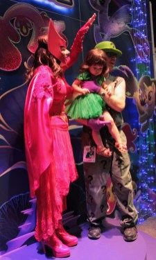 riddler poses with little poison ivy and a woman all in pink