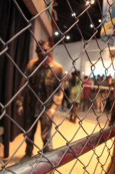 close up of a chain link fence as the walking dead approach behind it