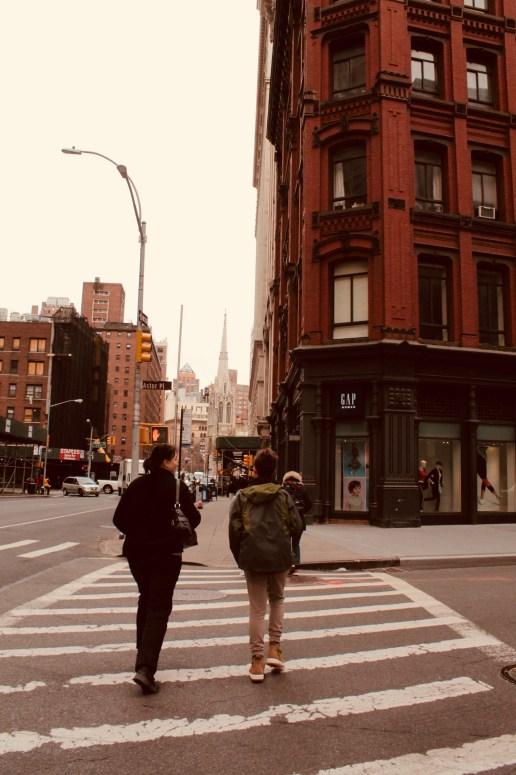 2 people walking down a street in New York city