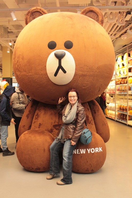 tourist in front of large stuffed bear with large round head reaching the store's ceiling