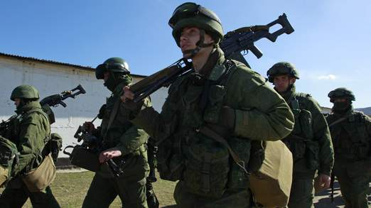 Military personnel, believed to be Russian servicemen, walk near the territory of a Ukrainian military unit in the village of Perevalnoye outside Simferopol