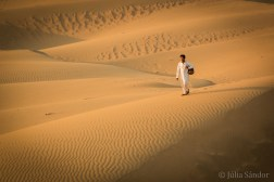 A musician walking the dunes of the Thar desert with his drum