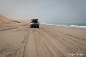 Driving on a thin landstrip between the dunes and the Sea