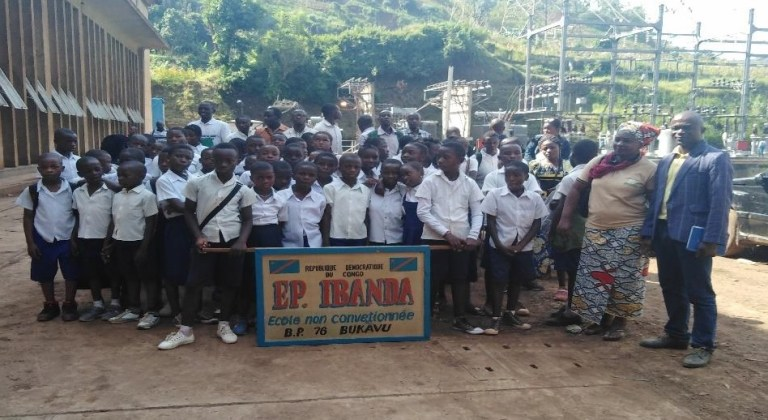 A large group of schoolchildren with two teachers and a banner for ecole non convetionee