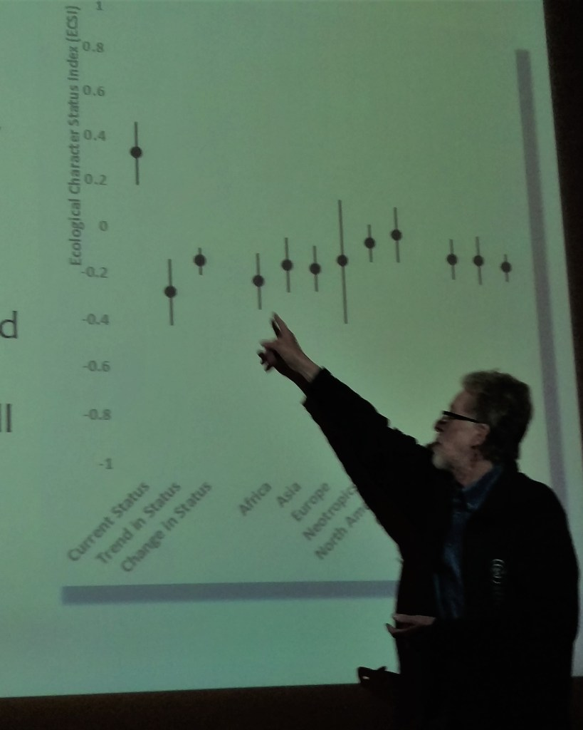 Man pointing at a scientific chart in a lecture hall