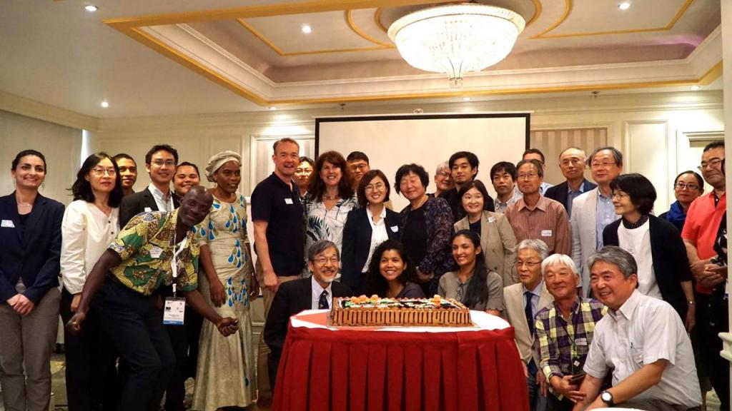 A happy group of people pose in a meeting room with a cake