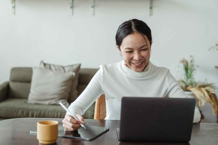 woman working at home and making video call on laptop