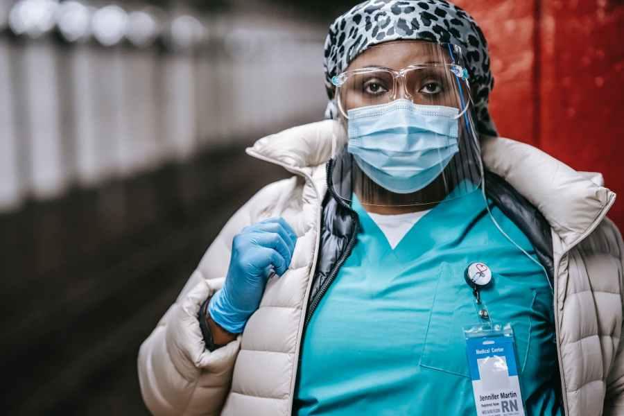 crop serious black nurse in mask standing on train platform