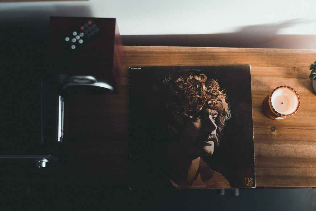 top view photography of vinyl album case near white tealight candle placed on brown table