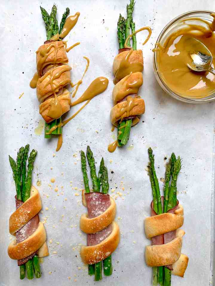 up close of 5 asparagus bundles with bowl with honey mustard inside