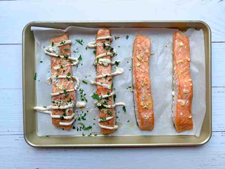 4 fully cooked salmon fillets, two of them are drizzled with yogurt tahini and parsley.