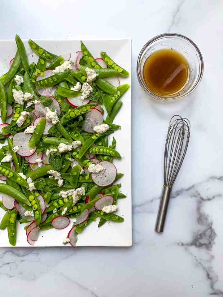 sugar snap pea salad on a white tray with bowl of lemon balsamic vinaigrette and whisk next to it