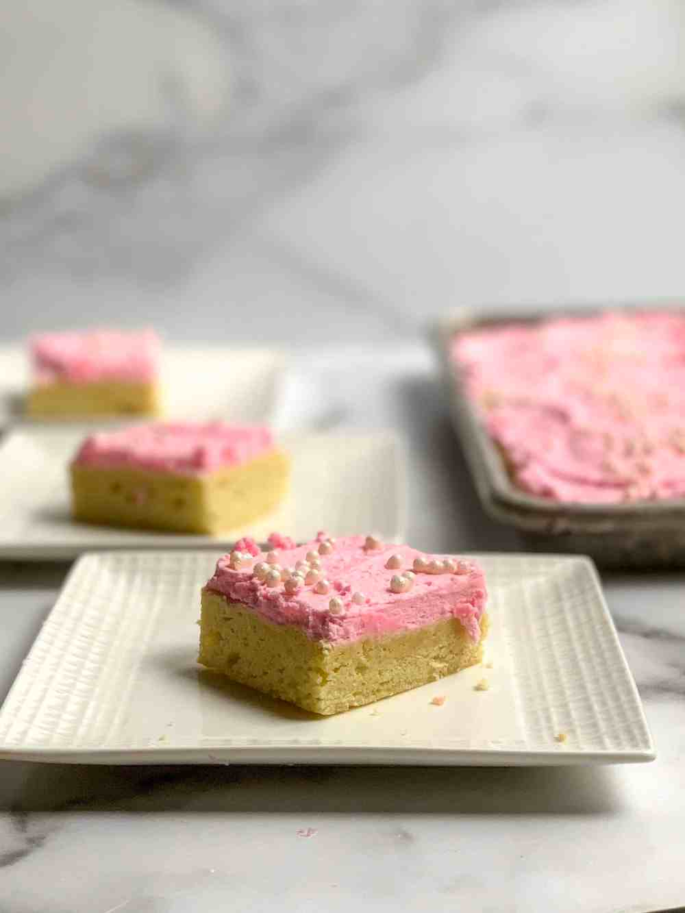 cut sugar cookie bars with fluffy frosting