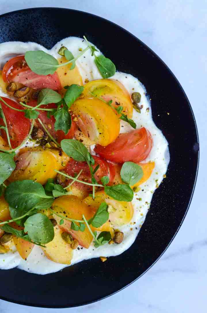 close up of tomato and peach salad with whipped goat cheese