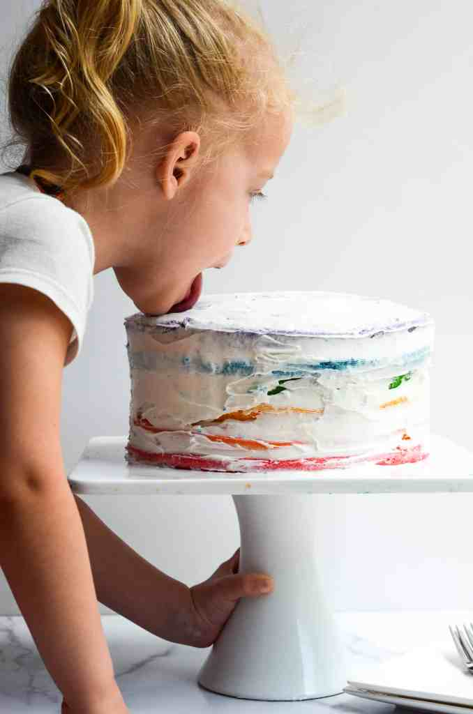 side view of child licking rainbow cake