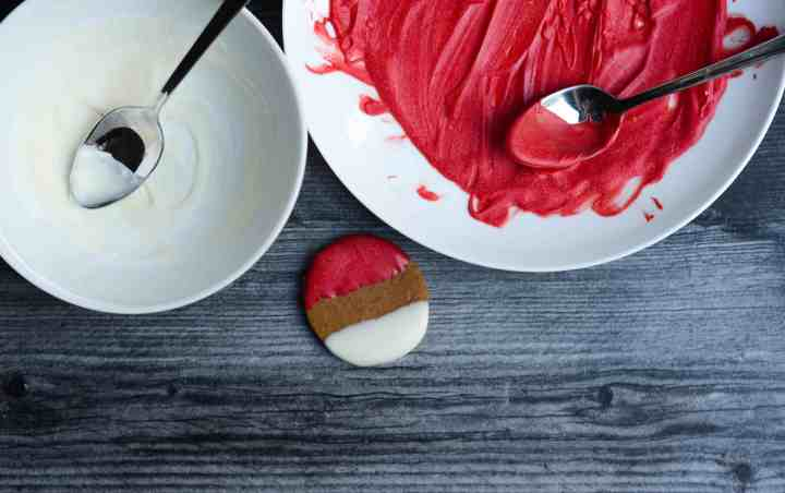 after melting both white chocolate and red candy melts, dip each side of the cookie in both. let cool on a rack.