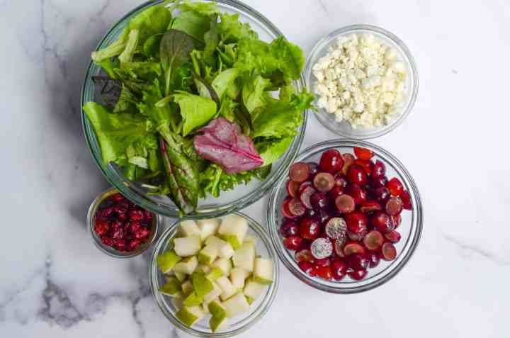 ingredients needed for the salad in bowls: mixed greens, grapes, gorgonzola, pears, dried cranberries, and pistachios