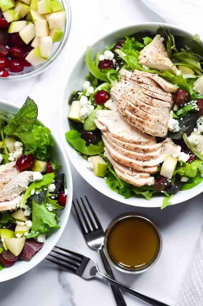 two bowls of copycat cosi signature salad with a bowl of apples and pears nearby