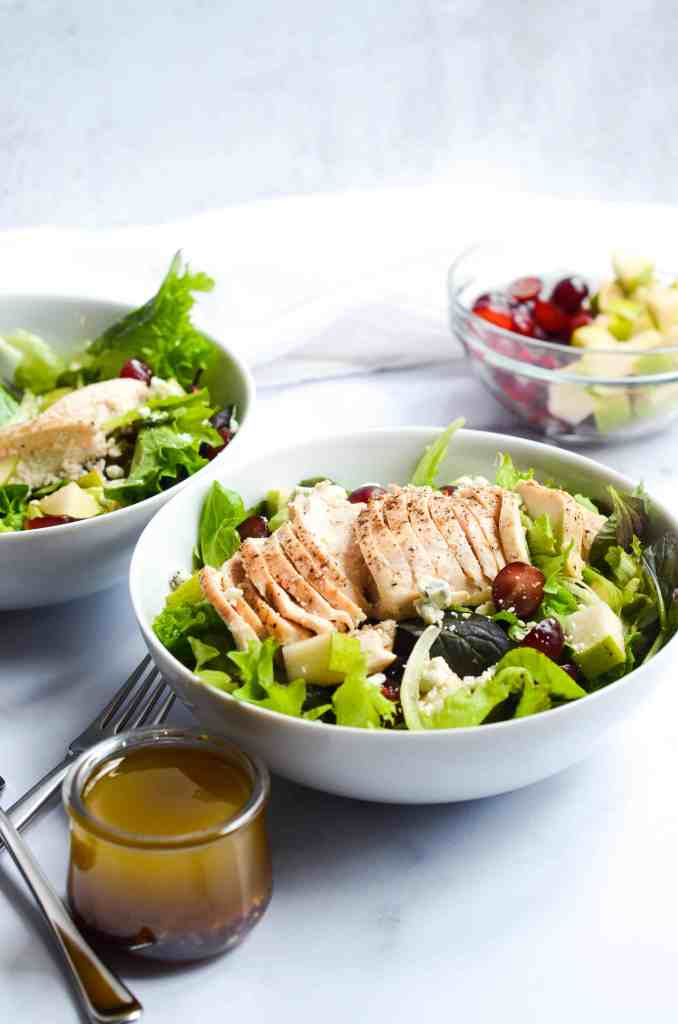 cosi signature salad in two bowls with a bowl of cut pears and grapes