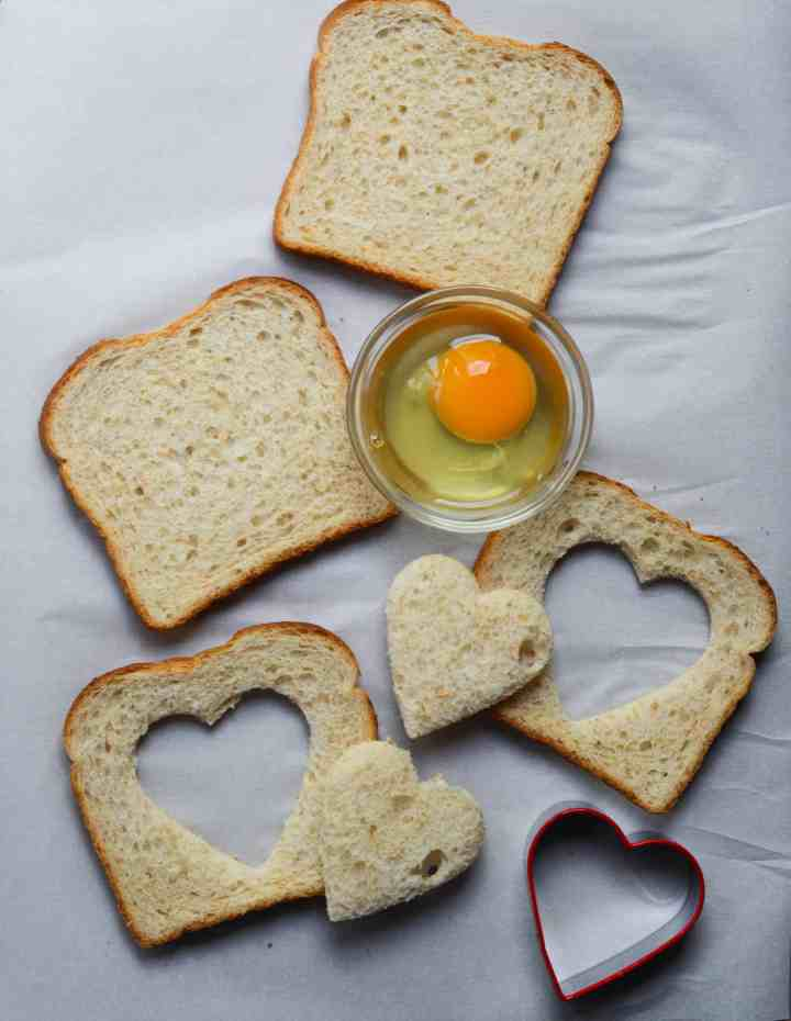 heart cookie cutter with hearts cut out of the toasts.  Egg is in a bowl waiting to be poured into the toasts.