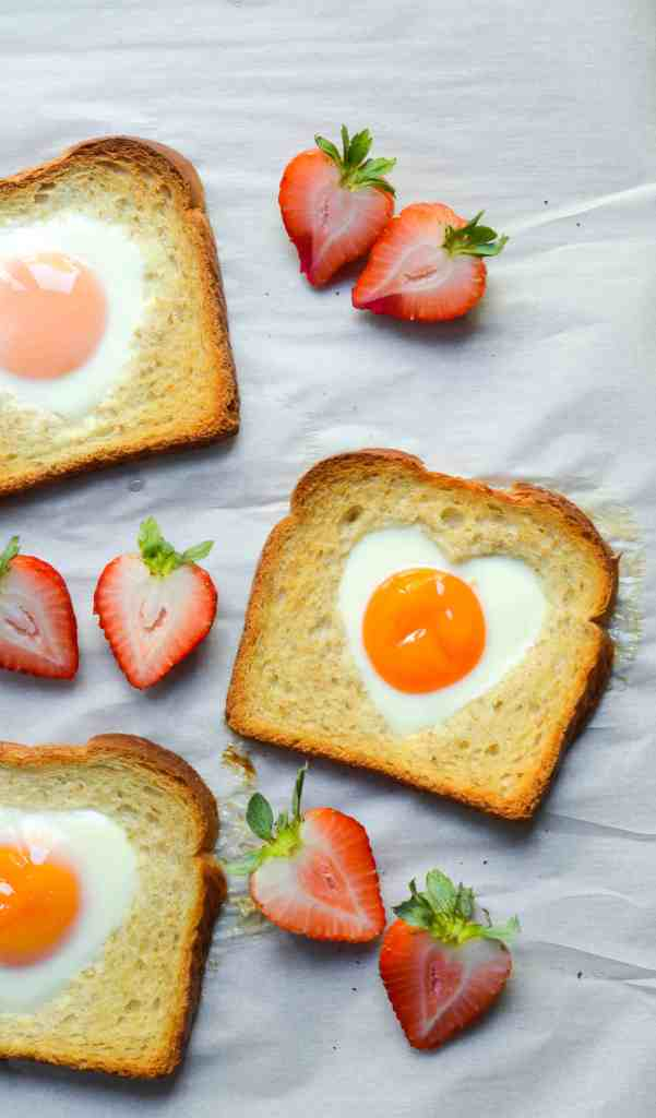 valentine's day eggs in a hole with strawberries on-parchment paper
