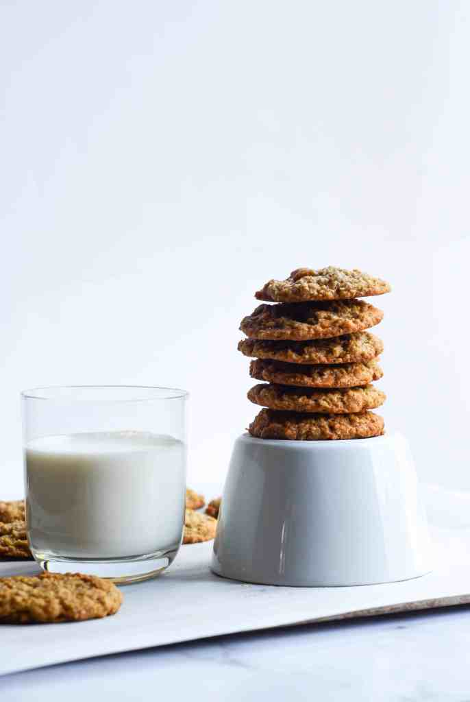 oatmeal butterscotch cookies stacked tall next to a glass of milk