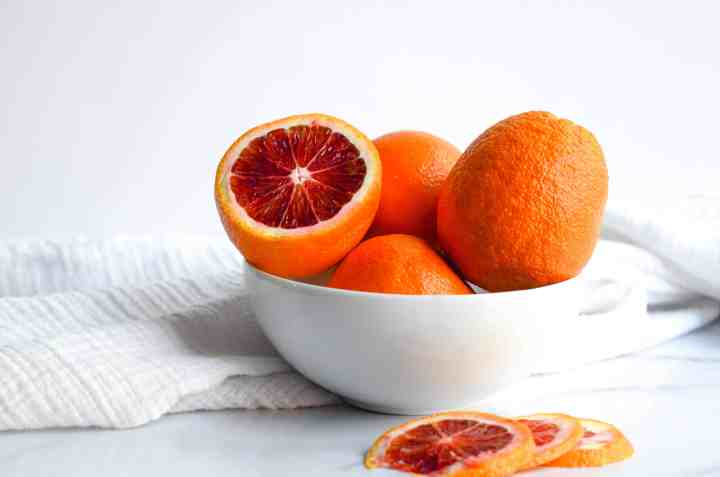 bowl full of blood oranges with one cut into