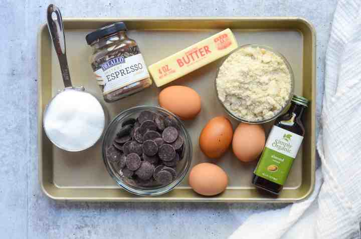 all necessary ingredients on a baking tray: butter, chocolate, sugar, eggs, almond flour, almond extract, and espresso powder.