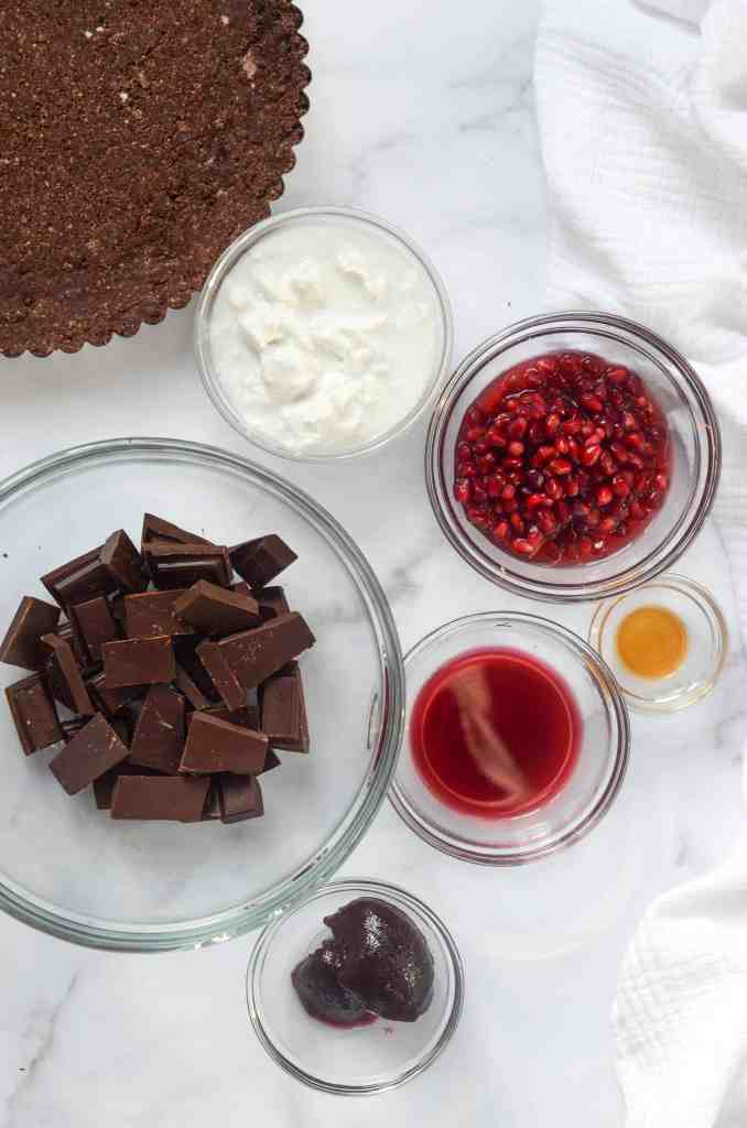 ingredients for chocolate filling in bowls: coconut milk, chocolate, pomegranate juice, vanilla extract, and raspberry preserves