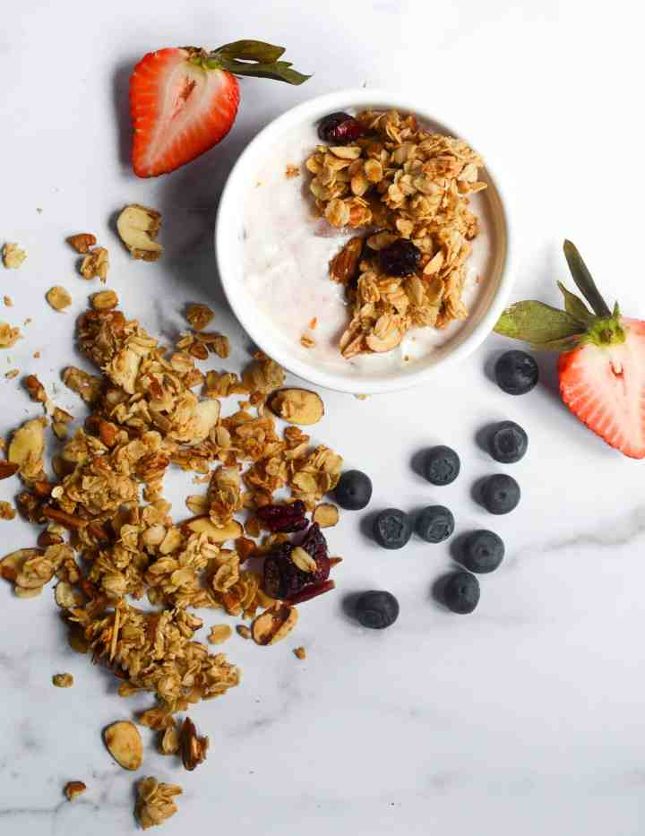 homemade granola in a bowl and scattered on counter with strawberries and blueberries