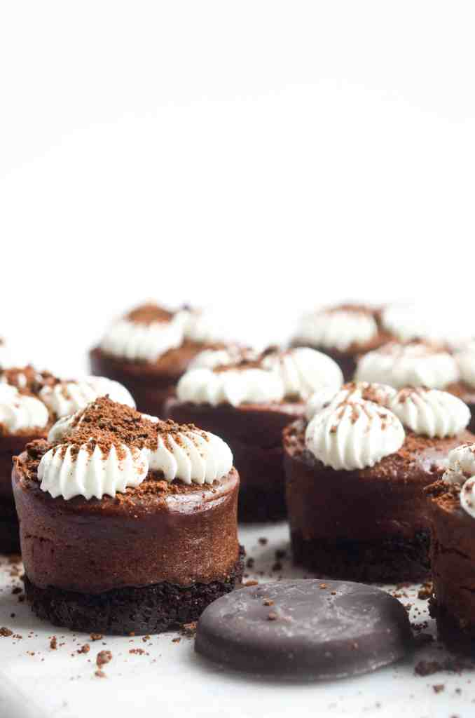 side angel of mini chocolate cheesecakes with whipped cream and a thin mint cookie next to it.