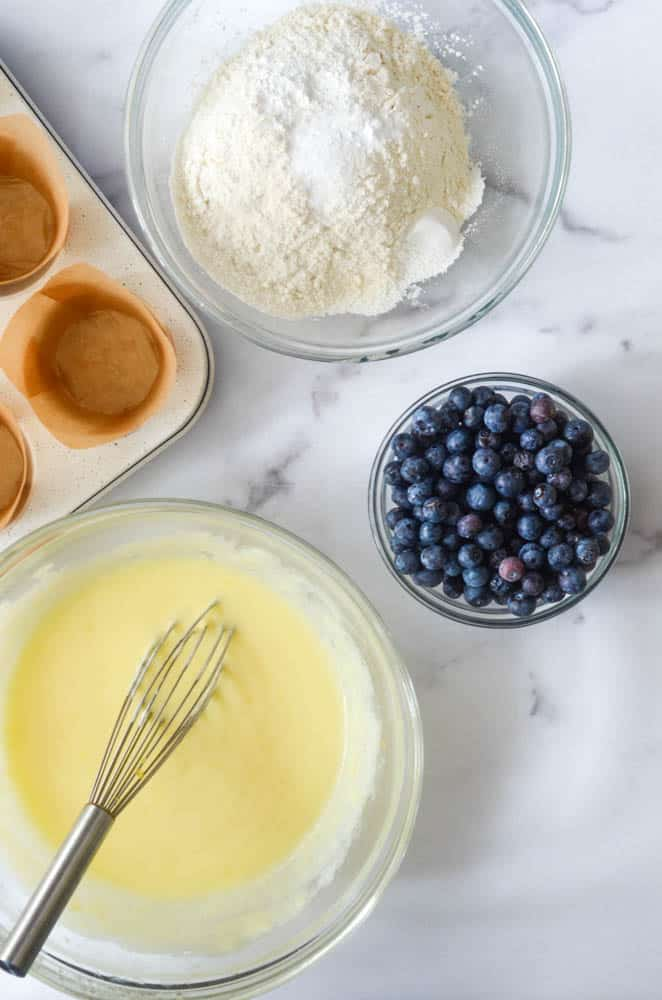 aerial view of bowl of wet ingredients with whisk, bowl of dry ingredients, and bowl of blueberries.