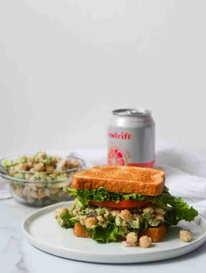 "chickpea ""chicken"" salad on white plate with can of soda and bowl of mixture in background"