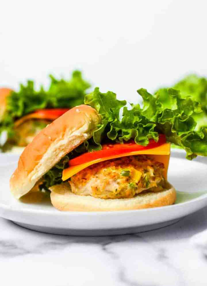 side shot of baked chicken burger on a bun with lettuce, tomato, and cheese.