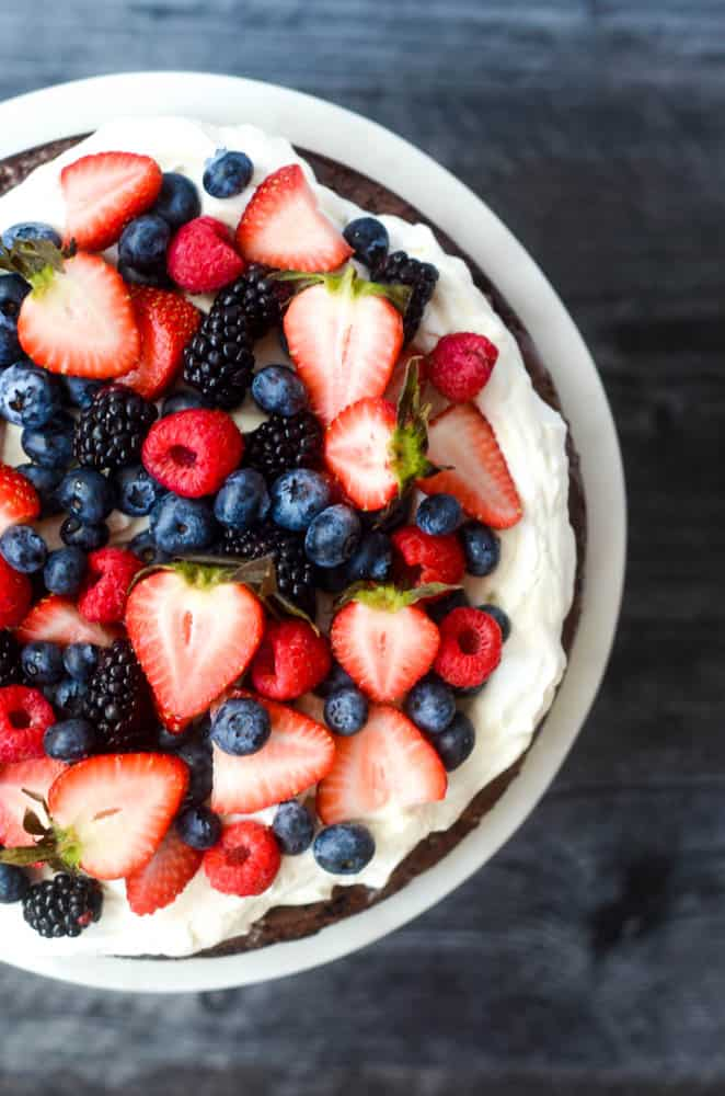 aerial view of mixed berries on top of brownie pizza against black background