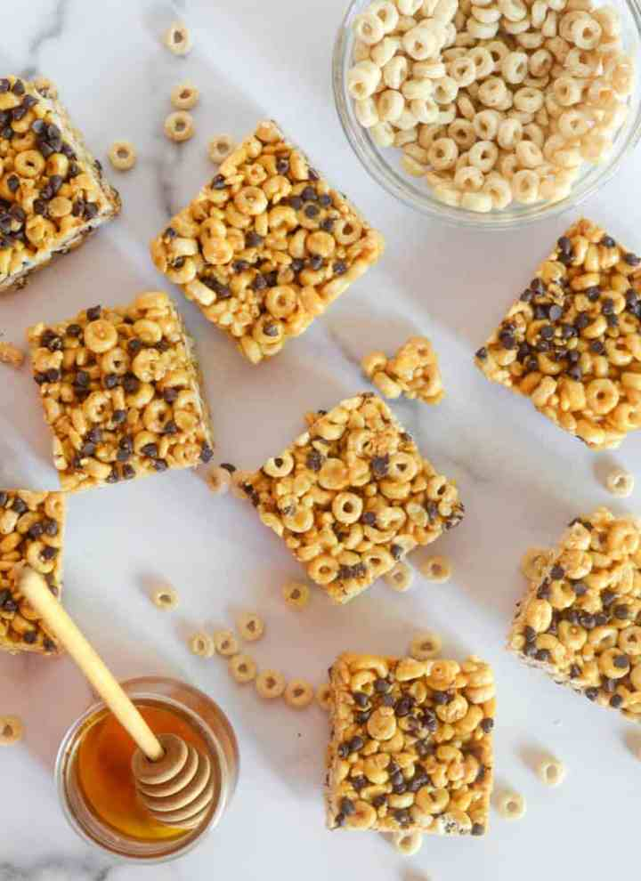 cut up cereal bar squares with jar of honey and bowl of cheerios on white background