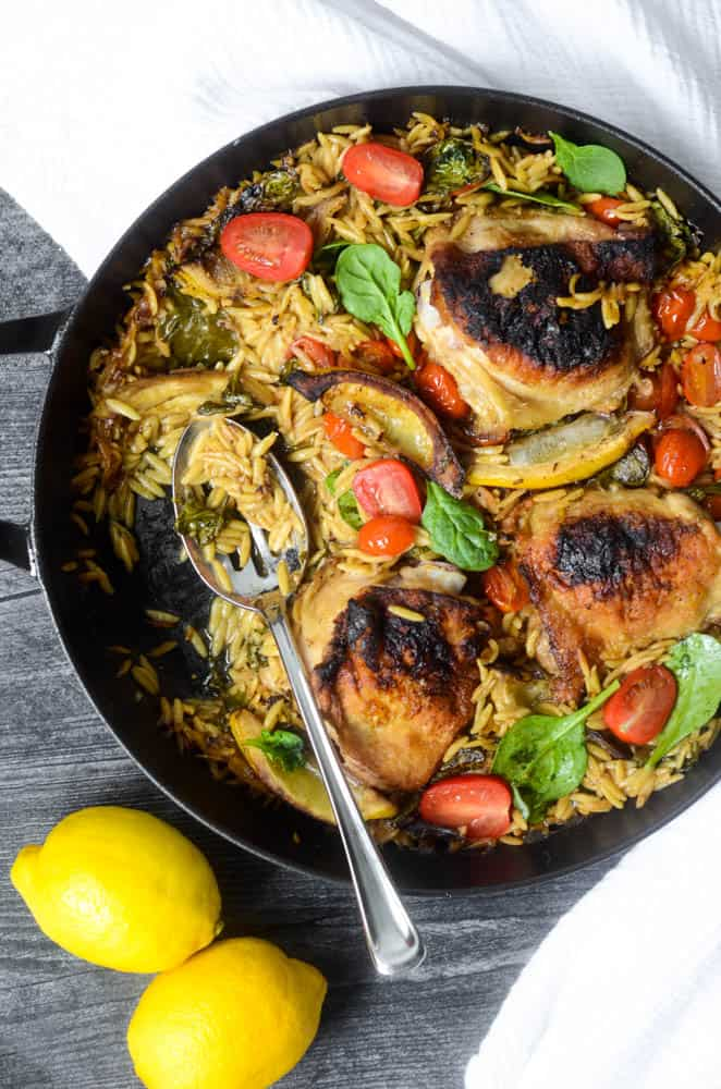 black skillet with lemon orzo chicken in it with spoon and portion taken out of pan