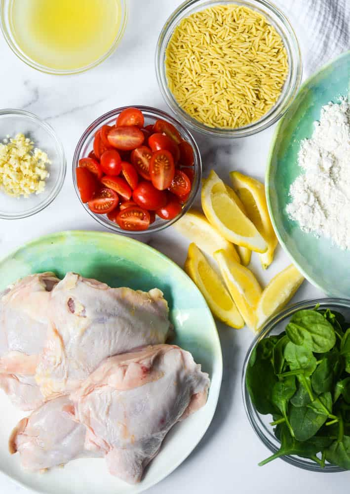 aerial shot of all ingredients needed: tomatoes, garlic, orzo, lemon, flour, spinach, and chicken thighs.