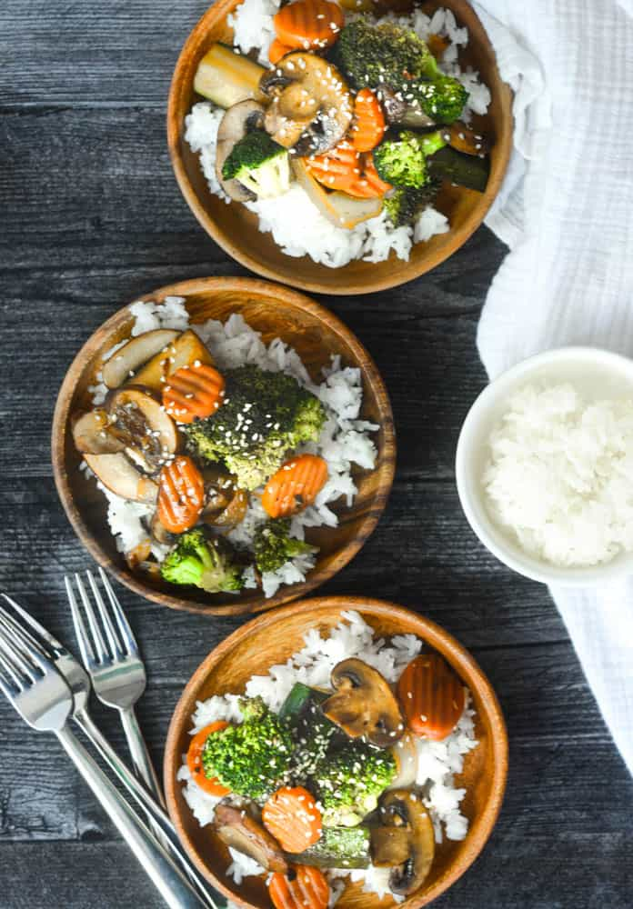 three wooden bowls of vegetables with forks and bowl of rice around bowls