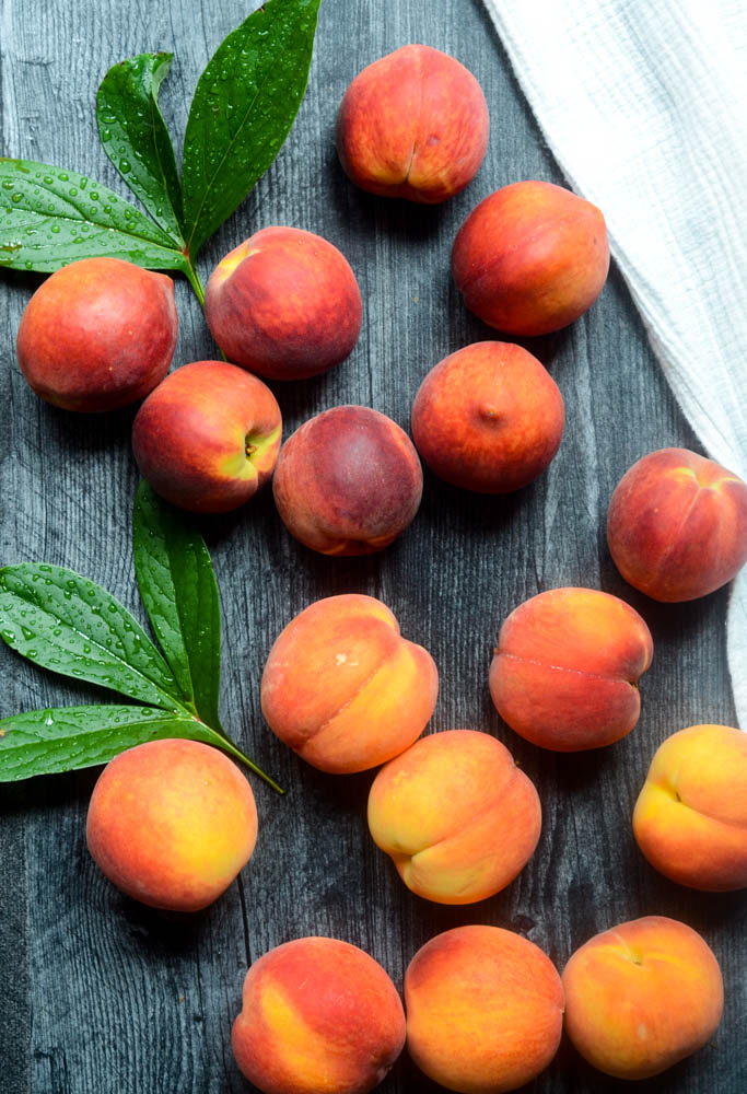 aerial view of peaches against a black wooden backdrop with green leaves.