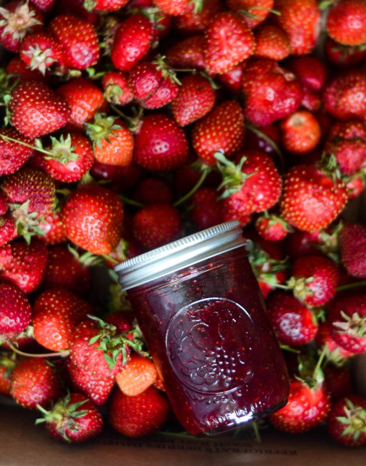 small batch strawberry jam in a jar in a bed of fresh strawberries