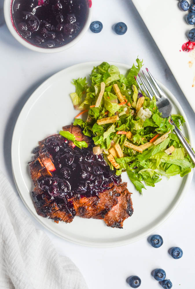 aerial shot of white plate with flank steak with blueberry sauce and side salad.