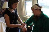 Helping Amy fit her bracelet.