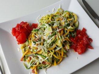 courgetti carbonara op bord met blokjes tomaat