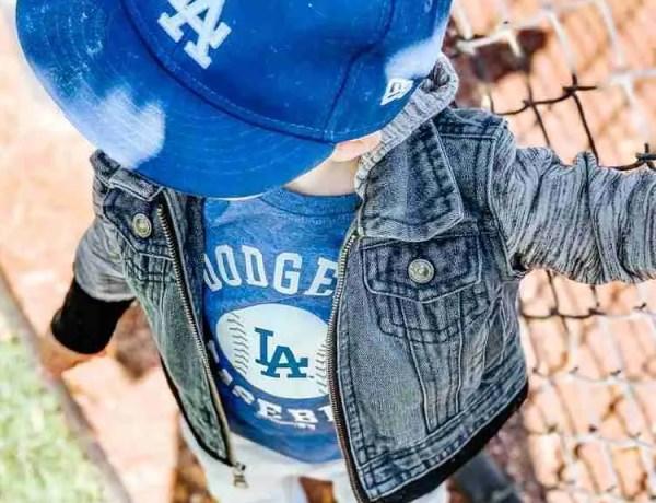 Toddler boy wearing Dodger baseball hat and Dodger baseball shirt standing by back drop of baseball field