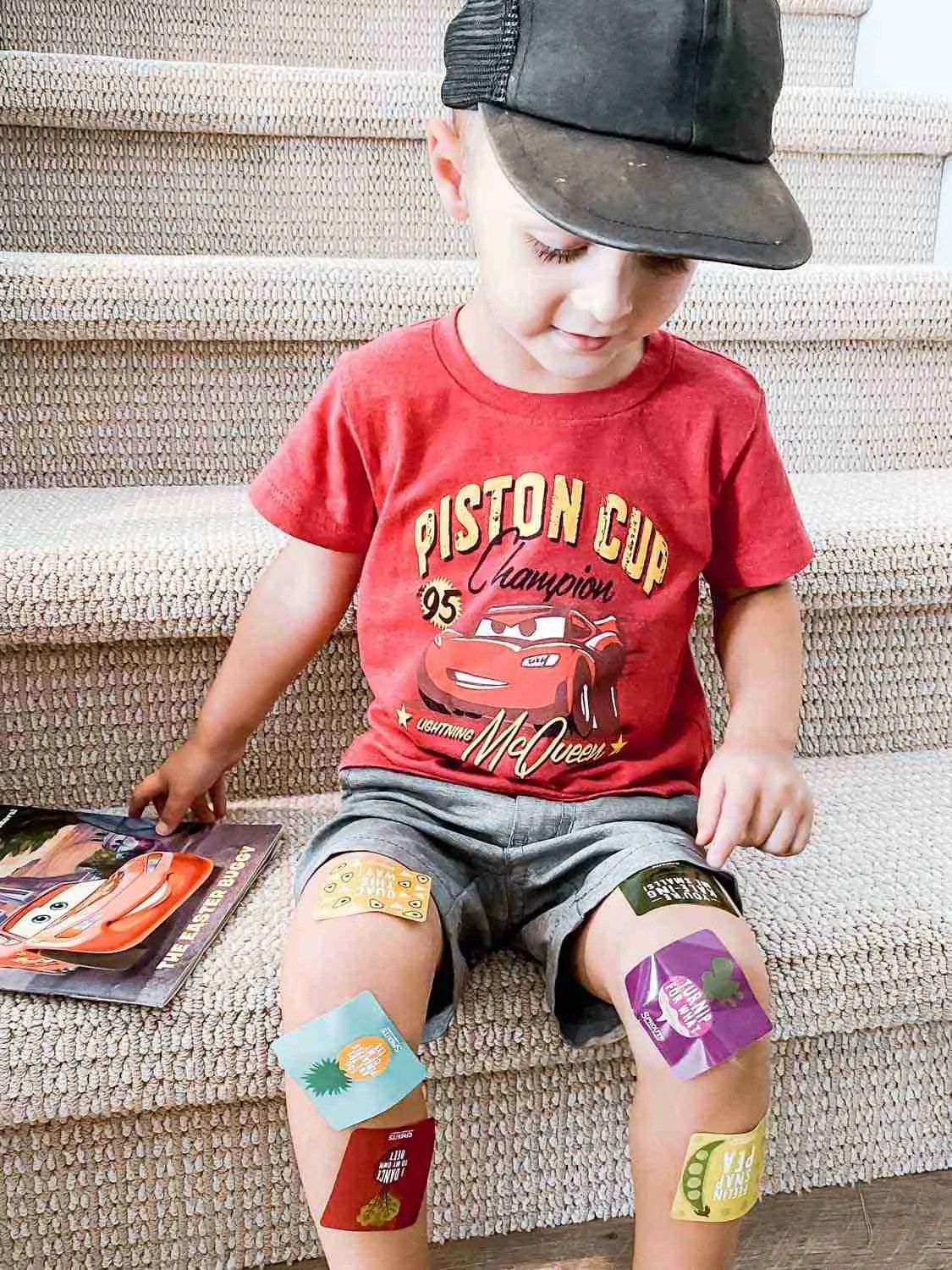 Little boy with stickers all over his legs and a smile on his face